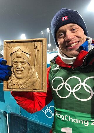 GAVE: Tarjei Bø fikk en gave i målområdet etter stafetten i går; en flott utskåret treplakett av ham. Foto: Roy Wahlstrøm