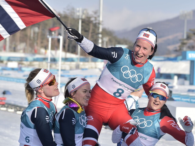 Marit Bjoergen lifted by her teammates after winning gold in South Korea.