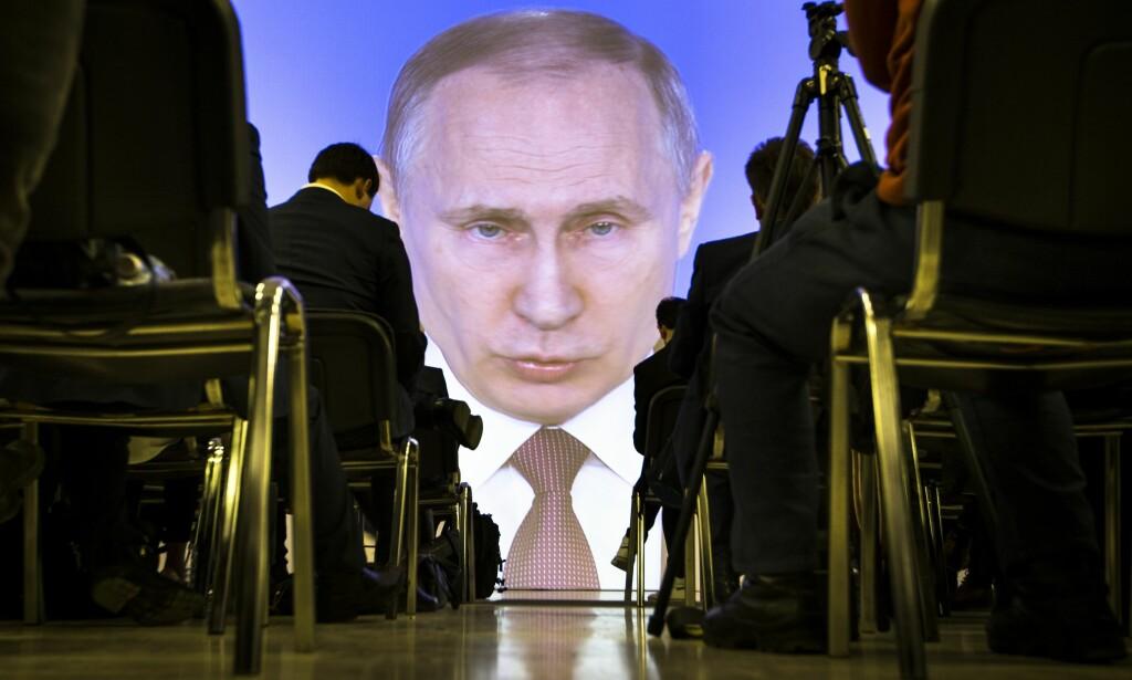 TØFF OG MILD: Journalister følger Putins tale fra et pressesenter i Moskva. Foto: AP / NTB Scanpix