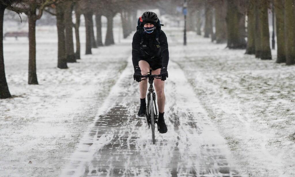 KLAR FOR «THE BEAST FROM THE EAST»: En syklist i et heller tvilsomt vinterantrekk tar seg gjennom Clapham Common i Storbritannia, hvor kuldestormen «Emma» treffer senere torsdag. Foto: NTB Scanpix