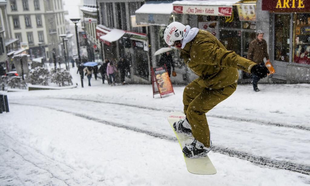 ALTERNATIVT FRAMKOMSTMIDDEL: Hva gjør man når det er vanskelig å komme seg fram til fots i snødekte Lausanne, Sveits? Man tar brettet. Foto: Jean-Christophe Bott/Keystone via AP