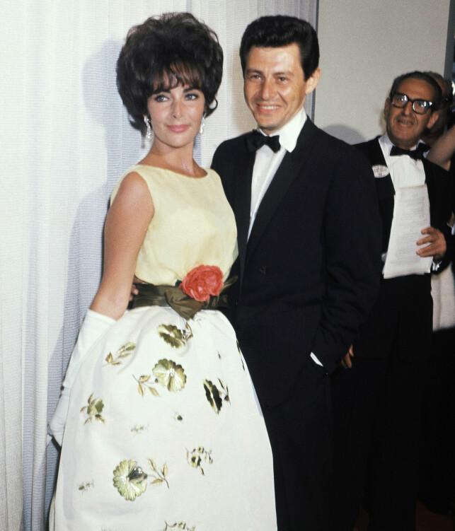 SJOKKSEIER: Her er Elizabeth og Eddie på rød løper før Oscar-utdelingen i 1961. Få timer senere vant hun pris for beste kvinnelige hovedrolle. Foto: NTB scanpix