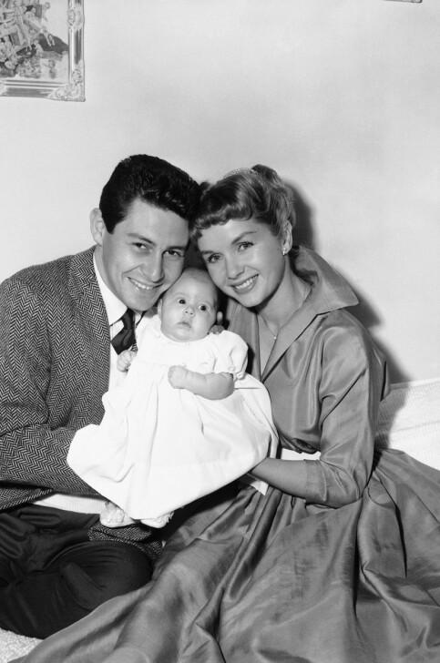 TO BARN: Eddie Fisher og Debbie Reynolds fikk to barn i løpet av ekteskapet, før det ble brutt opp med god hjelp av Elizabeth Taylor. Her er paret fotografert i 1957, med datteren Carrie - som siden skulle bli en verdenskjent skuespiller. Foto: NTB scanpix