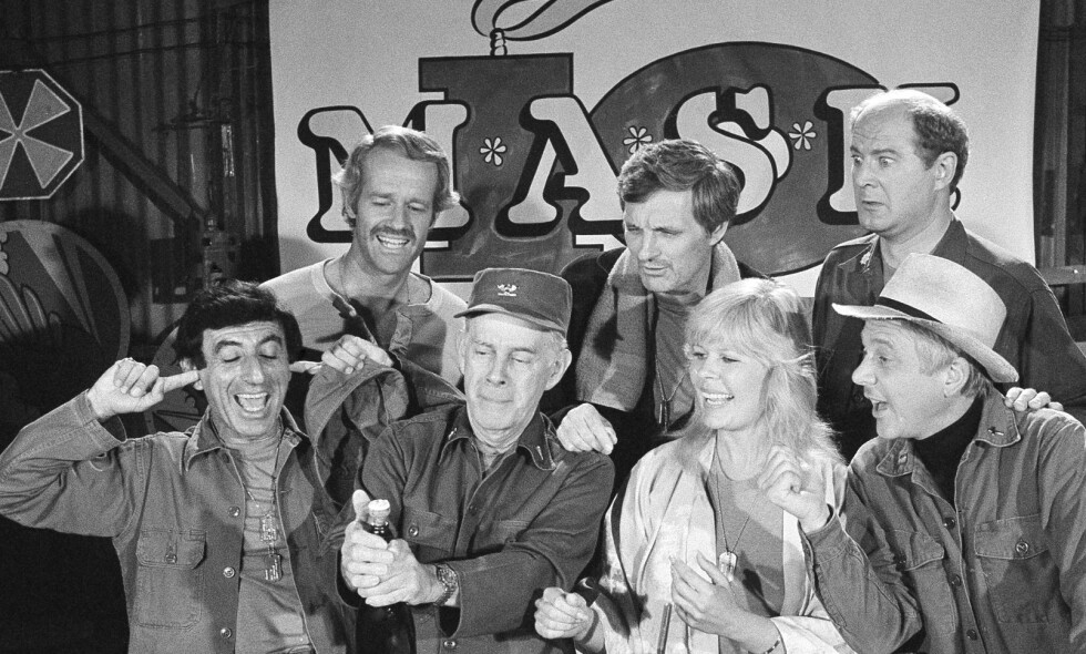 DØD: David Ogden Stiers (øverst til høyre) spilte i den svært populære amerikanske komiserien Mash. Her er han sammen med noen av medskuespillerne, Jamie Farr (foran fra venstre), Harry Morgan, Loretta Swit, William Christopher, og bak fra venstre: Mike Farrell og Alan Alda, i 1981. Foto: AP Photo/Huynh, File