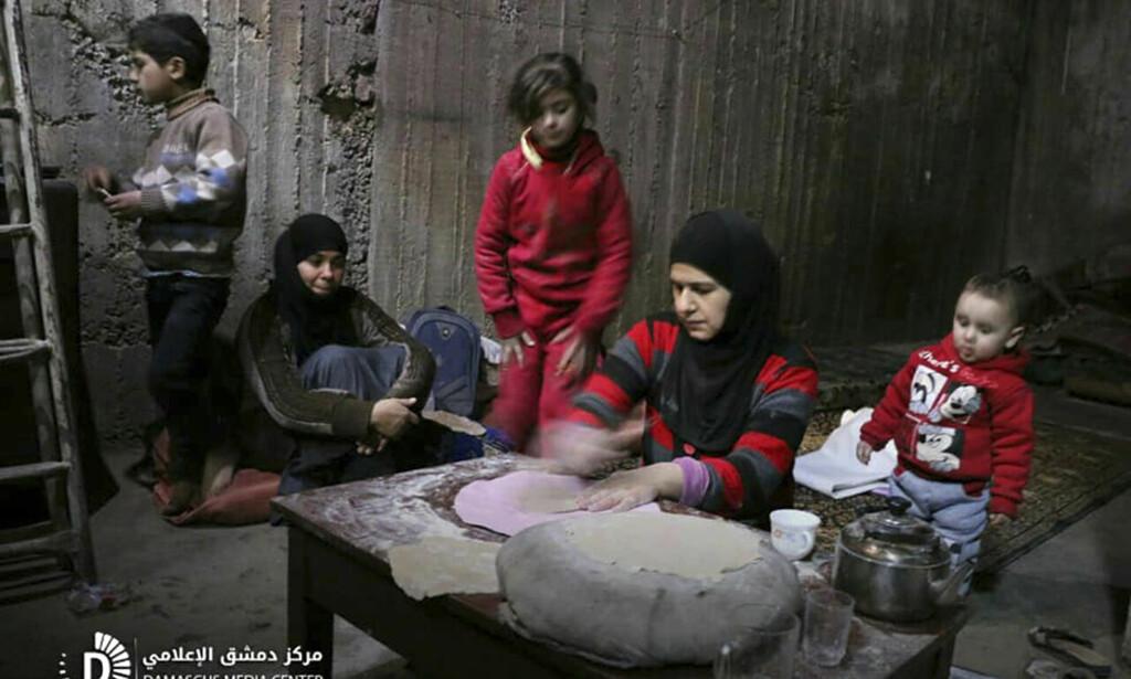 <b>STOR NØD:</b> Bildet viser en syrisk kvinne som baker brød i et bomberom i Øst-Ghouta, utenfor Damaskus. Foto: Syrian Damascus Media Center / AP / NTB Scanpix