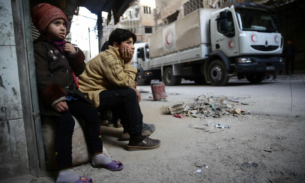 UT OVER SIVILE: Barn ser på at at hjelpekonvoier ankommer Øst-Ghouta. Foto: Scanpix /REUTERS/ Bassam Khabieh