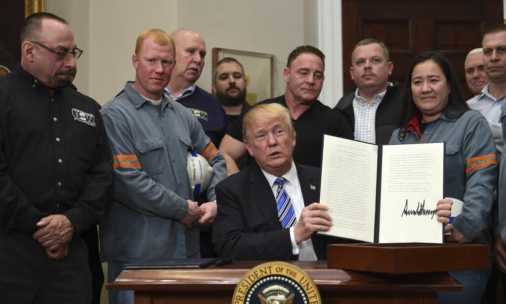 INNFØRER TOLL: Omgitt av amerikanske stålarbeidere undertegnet president Donald Trump en ordre om å innføre toll på stål og aluminium. Foto: AP / NTB scanpix