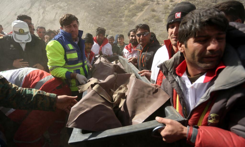 FLYKRASJET: Redningsarbeidere frakter døde bort etter flystyrten i Iran søndag. Foto: REUTERS/Tasnim News Agency