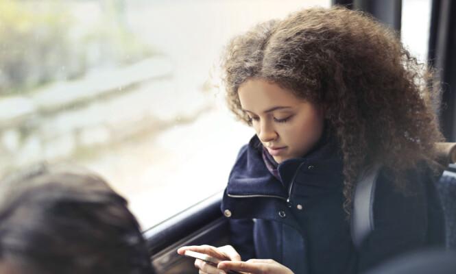 BUSS = MOBIL: Med blikket festet på mobilen sitter vi i vår egen verden, og tar sjeldnere og sjeldnere blikket opp for å titte på verden rundt oss. FOTO: NTB Scanpix