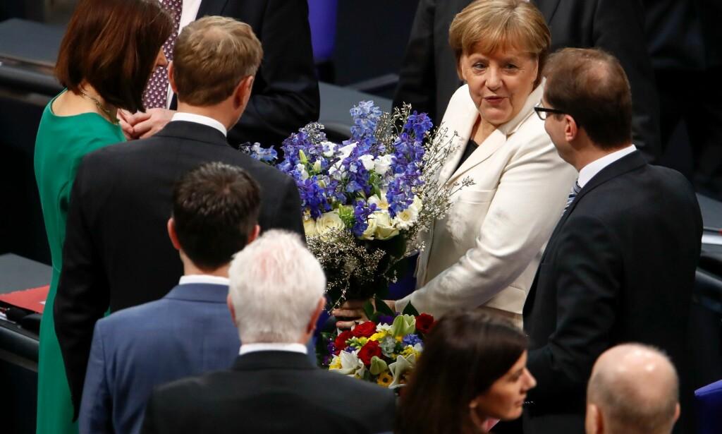GRATULERT: Angela Merkel gratuleres med blomster onsdag, etter å ha blitt gjenvalgt som forbundskansler i Tyskland.Foto: Odd Andersen/ AFP/ NTB Scanpix