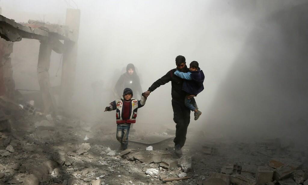 PÅ FLUKT FRA BOMBENE: En far tar seg fram i støvskya med barna etter et luftangrep i Øst-Ghouta. Siden 18. februar har regjeringsstyrker drevet en offensiv i området. På den tiden har nesten 1400 personer blitt drept. Foto: NTB scanpix