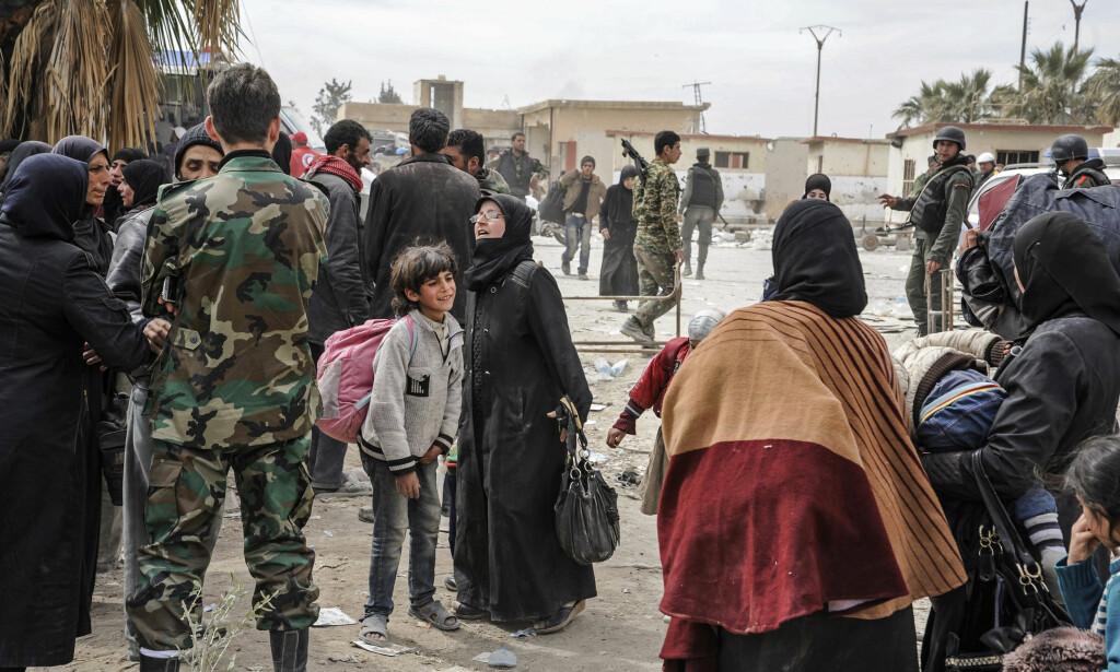 HJELP: Syriske soldater har blitt satt til å hjelpe sivile flyktninger like ved Øst-Ghouta. Foto: AP / NTB Scanpix