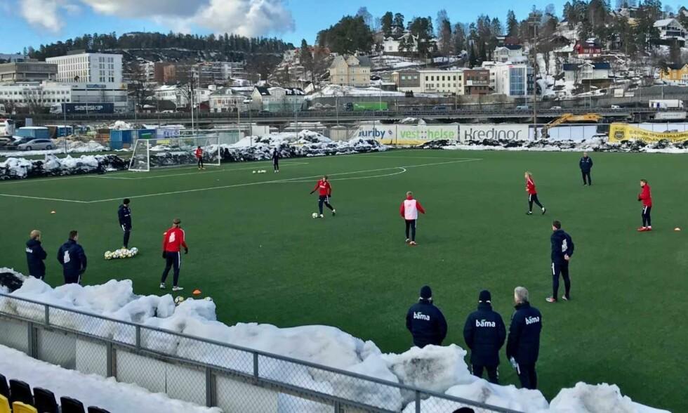 GODT BEFOLKET PÅ SIDELINJA: Det var flere fra støtteapparatet (i blått) enn spillere (i rødt) på mandagens trening i Sandvika. I bakgrunnen dundret trafikken fra E18. Foto: Tore Ulrik Bratland