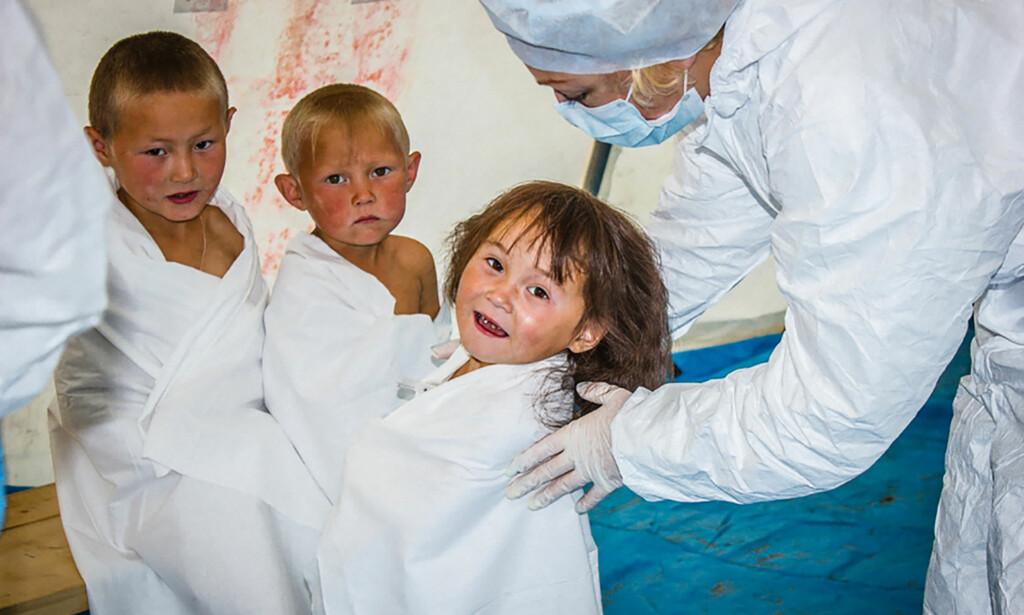 SMITTER MENNESKER: En lege undersøker russiske barn under utbruddet i 2016. Foto: AFP / Russian Emergency Ministry / NTB Scanpix