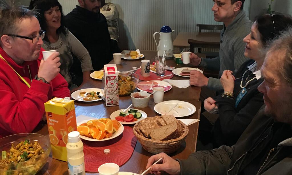 Frivillige og gjester er samlet rundt et av frokostbordene i Vår Frue Kirke i Trondheim på lørdag. (Foto: Hanne Alstad)