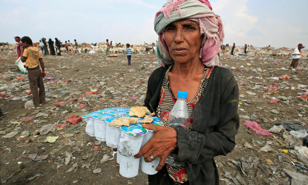 EKSTREM FATTIGDOM: Denne kvinnen er som flertallet av de over 29 millioner innbyggerne i Jemen: Tre år inn i krigen er 80 prosent av innbyggerne helt avhengig av humanitær hjelp for å overleve. Disse utgåtte yoghurt-pakkene skal hjelpe denne kvinnen og hennes familie til å overleve, og er funnet på søppelhaugen ved havnebyen Hodeida i Jemen. Foto: Abduljabbar Zeyad / Reuters / Scanpix