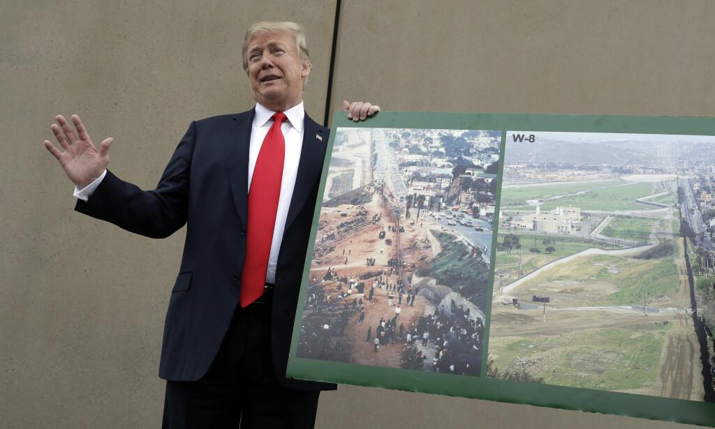 PÅ BEFARING: President Donald Trump viser fram et bilde av grenseområdet mot Mexico idet han inspiserer prototyper som er bygd av den planlagte grensemuren. Foto: Evan Vucci / AP / NTB scanpix