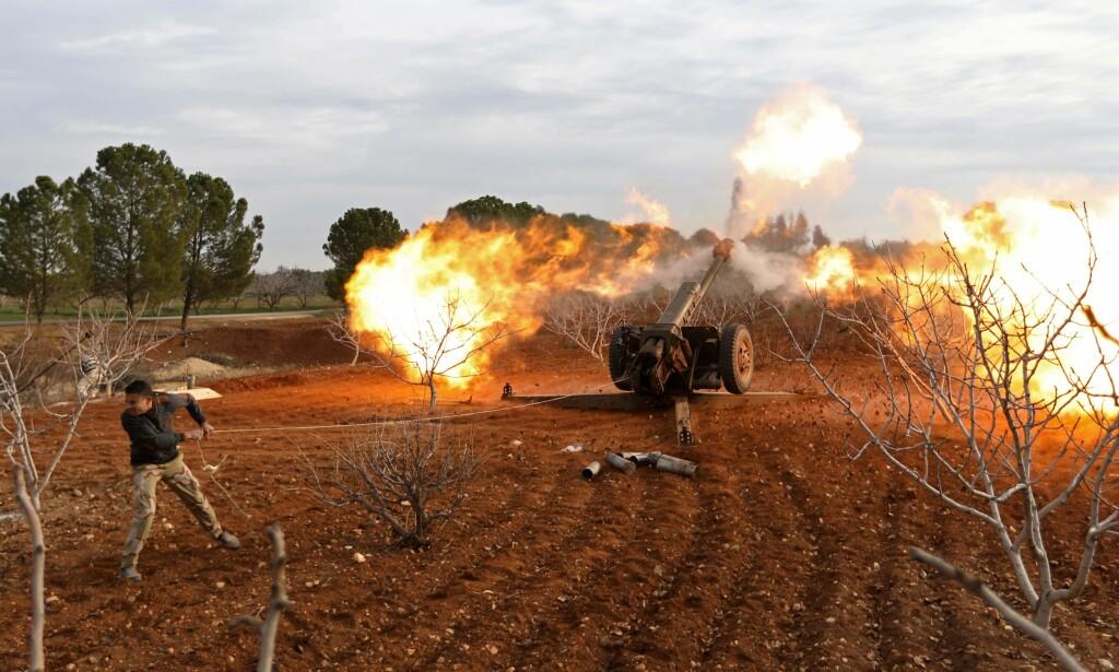 MIDT I ILDLINJA: En syrisk opprørssoldat fyrer av en kanon mot syriske regjeringssoldater ved en landsby i Idlib-provinsen. Bildet er tatt 11. januar. Foto: Omar Haj Kadour/AFP/NTN Scanpix