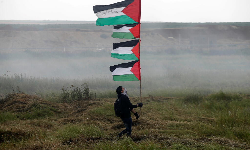DEMONSTRASJON: En demonstrant holder palestinske flagg høyt opp, øst for Gaza by. Foto: Mohammed Salem / Reuters / Scanpix
