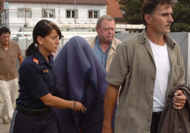 SKJERMET: 23. august 2006 dukket en kvinne opp fra intet i Strasshof utenfor Wien og hevdet at hun var Natascha Kampusch, som åtte år tidligere hadde blitt kidnappet. Pressen var raskt på stedet. Her blir kvinnen eskortert bort fra området av politiet. Foto: Helmut Stamberg / AP / NTB Scanpix