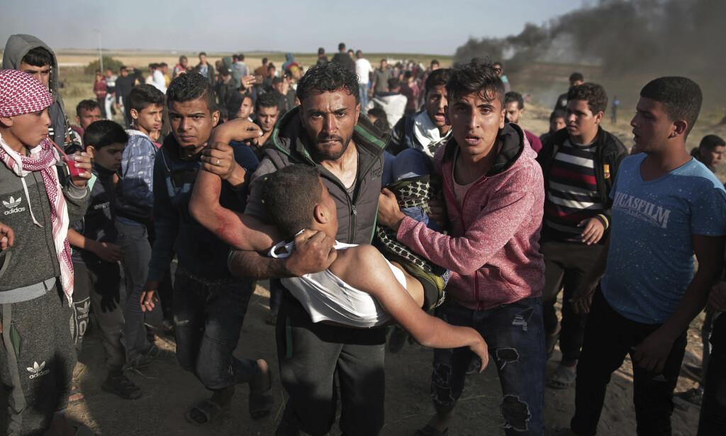 SKUTT: Palestinske demonstranter bærer bort en mann som ble skutt av israelske soldater under protester øst for Gaza by lørdag. Foto: Khalil Hamra / AP / NTB scanpix