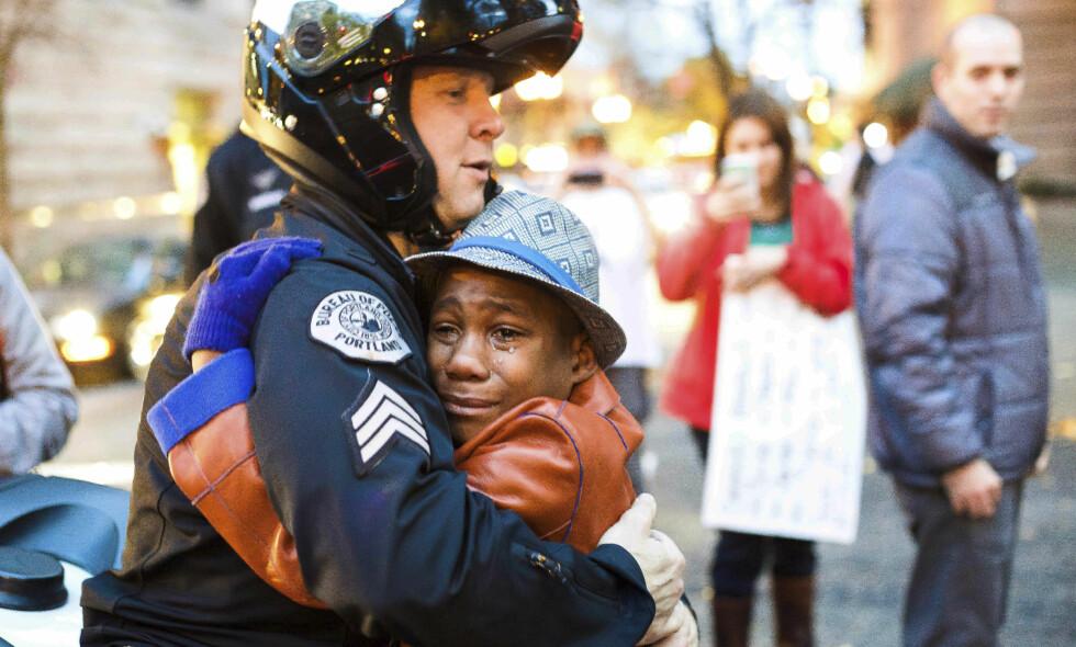 BERØMT BILDE: Her får en tolvårig Devonte Hart trøst av politimannen Bret Barnum under en demonstrasjon i Portland, i kjølvannet av drapet på Michael Brown i Ferguson. Foto: Johnny Huu Nguyen / AP / NTB Scanpix