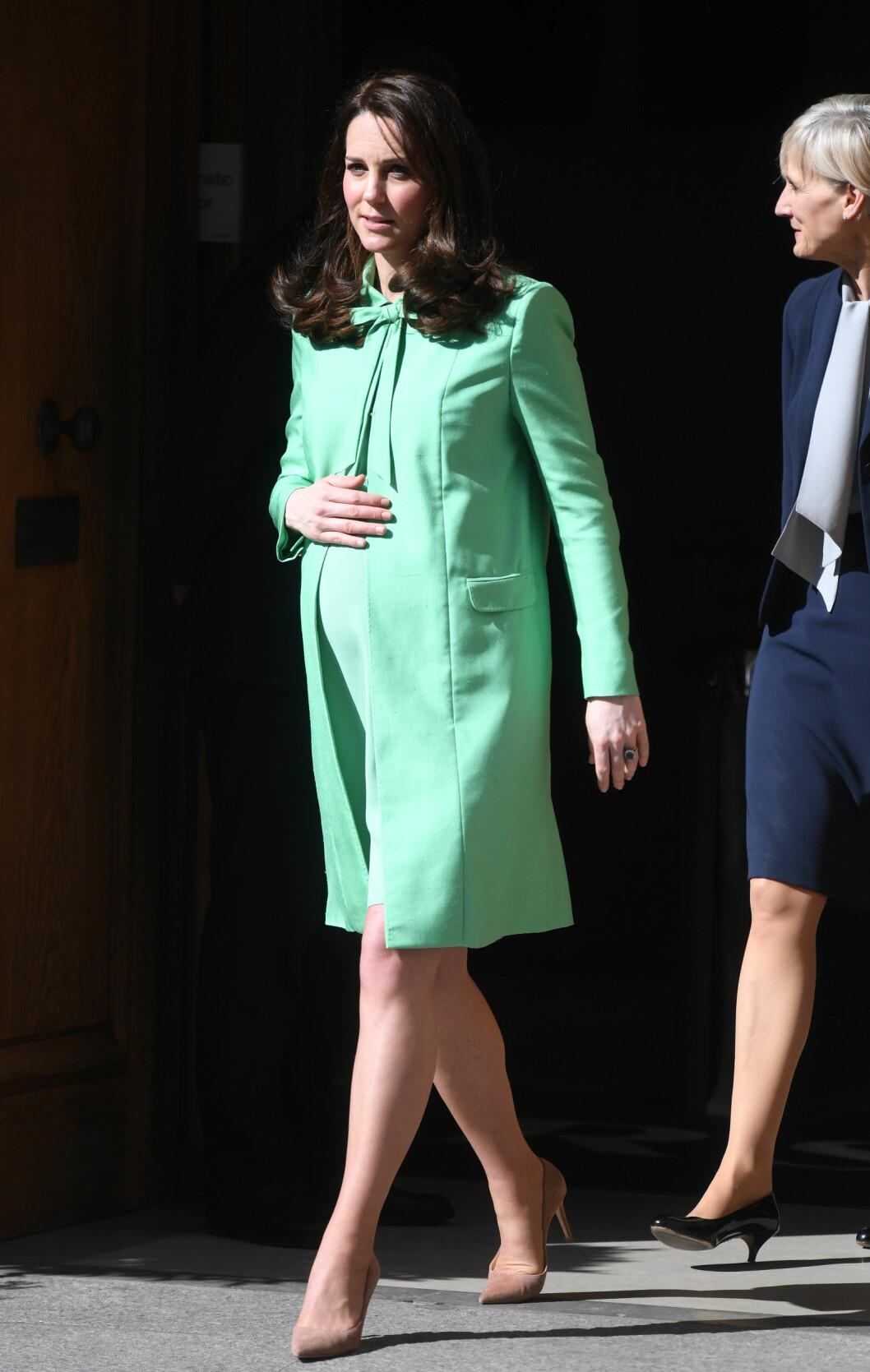 STRØK SEG PÅ MAGEN: Høygravide hertuginne Kate på vei ut av et arrangement på Royal Society of Medicine i London 21. mars. Foto: NTB Scanpix