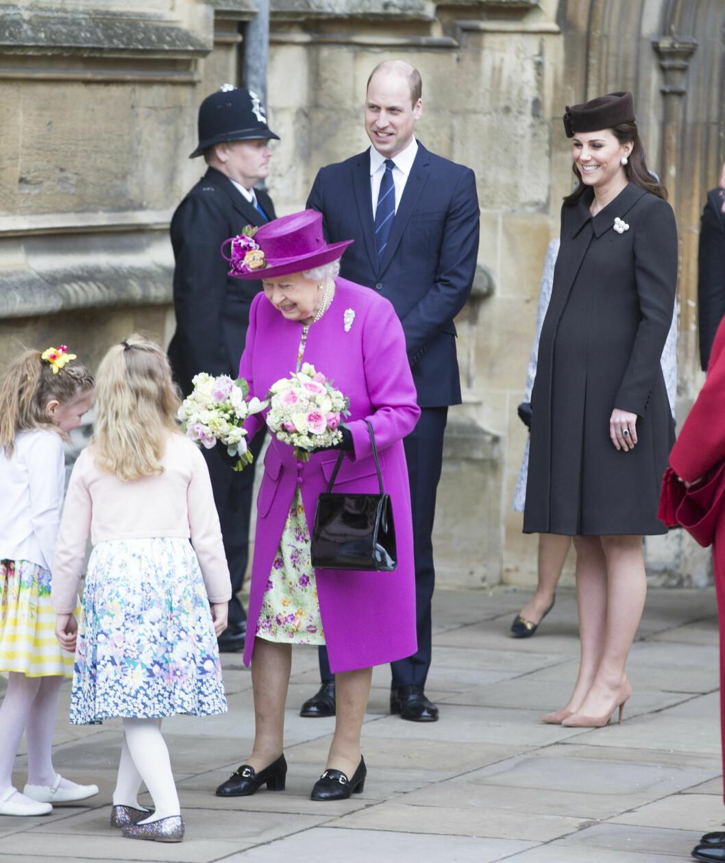 PÅSKEGUDSTJENESTE: Hertuginne Kate var til stede under 1.påskedagsgudstjenesten i St. George's Chapel på Windsor Castle med hele den britiske kongefamilien. Her tar dronning Elizabeth imot blomster fra to fremmøtte jenter. Foto: NTB Scanpix