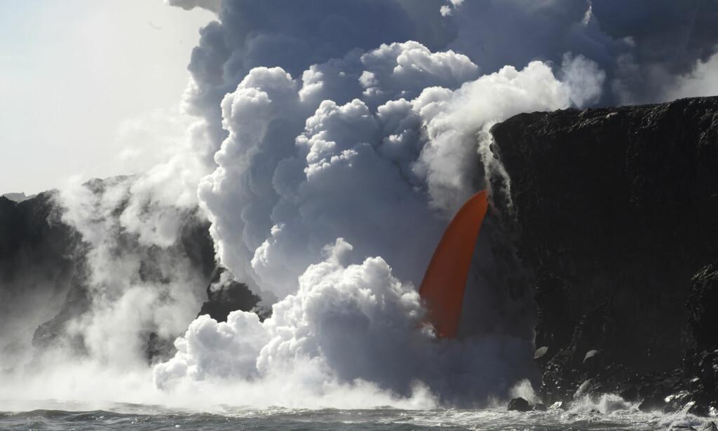 UT MOT HAVET: En glovarm, tyntflytende lavastrøm fra vulkanen Kilauea renner over en klippe på sørøstsiden av Big Island, Hawaii. Foto: Shane Turpin/ AP/ NTB Scanpix