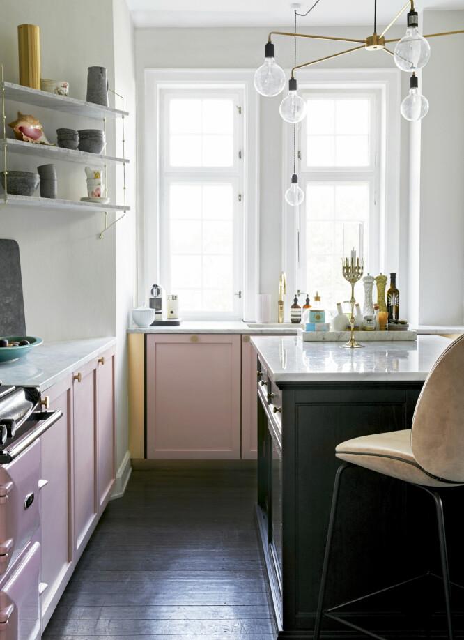 KJØKKENET ETTER: Familien valgte utradisjonelle rosanyanser til rommet. De svarte gulvene gir kontrast, og på den ene veggen pynter store fliser med botaniske motiver opp. Benkeplatene er i marmor, og overalt står kjøkkenting og reisefunn framme. FOTO: Dianna Nilsson