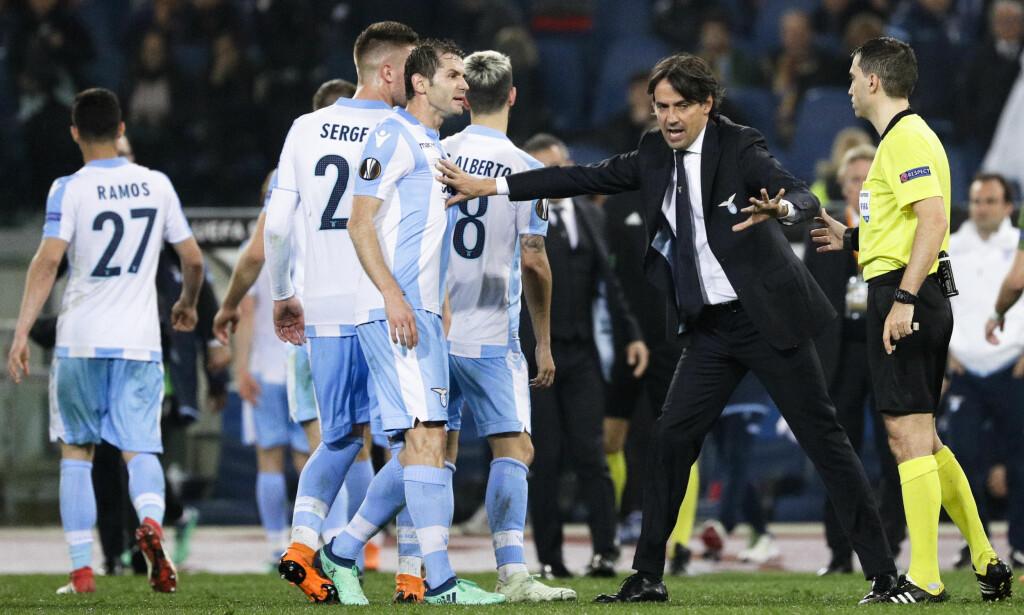 Simone Inzaghi holder Marco Parolo unna dommer Ovidiu Hategan. Flere Lazio-fans Foto: AP / Gregorio Borgia
