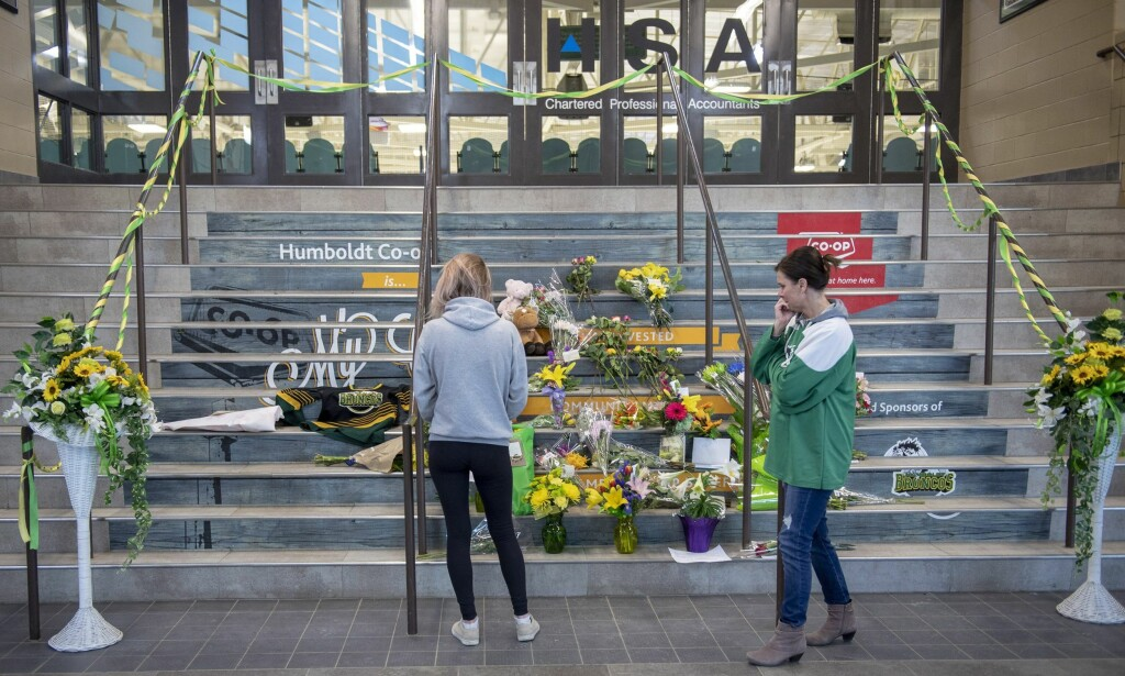 People gather at a memorial set up on the stairs that lead to Elgar Petersen Arena in Humboldt, Sask. on Saturday, April 7, 2018. Investigators are still trying to piece together what happened when a tractor-trailer collided with a hockey team bus at a Saskatchewan highway intersection in a horrific crash that killed 15 people, including players and the coach of the Humboldt Broncos. THE CANADIAN PRESS/Liam Richards