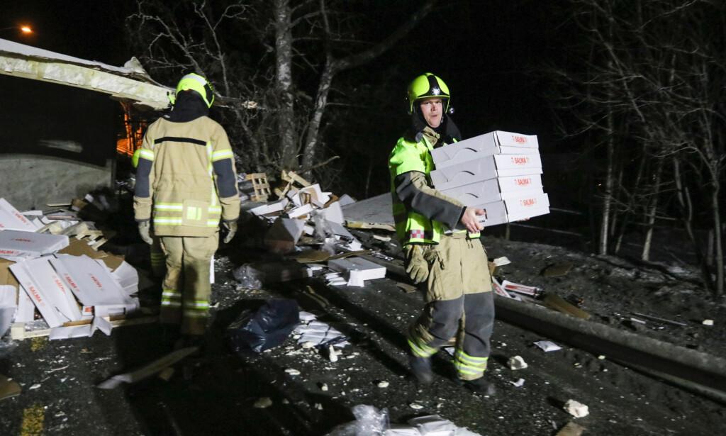 RYDDER: Brannvesenet fikk litt av en jobb med å rydde opp etter velten. Kasse på kasse med Salma-laks måtte ryddes bort, i tillegg til at hengeren på traileren må kappes av. Foto: Vegard M. Aas / Presse30.no