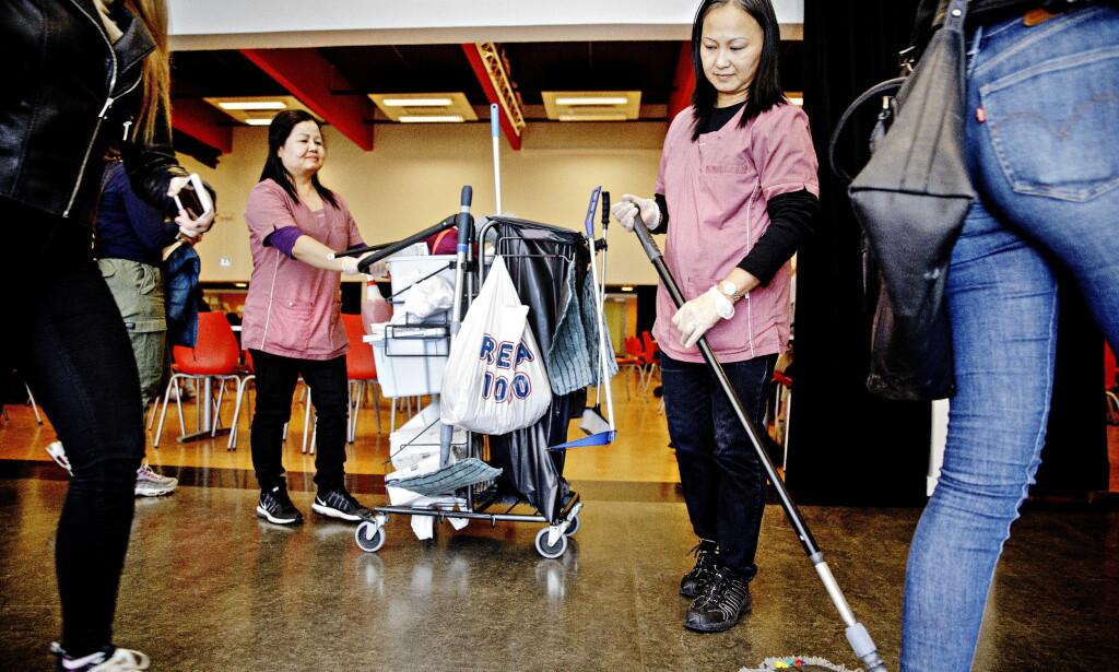 SYNES I MILJØET: Nå har renholderne på Greveskogen skole i Tønsberg fått uniformer, så de synes i skolemiljøet. En pekefinger fra Pailin Songkhla (til venstre) gjør at eleven som hadde tenkt å legge igjen salatboksen på bordet, plutselig husker å ta den med til søppelkassen. Til høyre ses Lien Bich Thi Nguyen. Foto: Nina Hansen