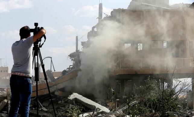 UTBOMBET: Et journalist filmer ruinene av en bygning som skal ha vært del av et syrisk forskningssenter nord for Damaskus, og som var mål for luftangrepet i natt. Foto: Louai Beshara / AFP / NTB Scanpix