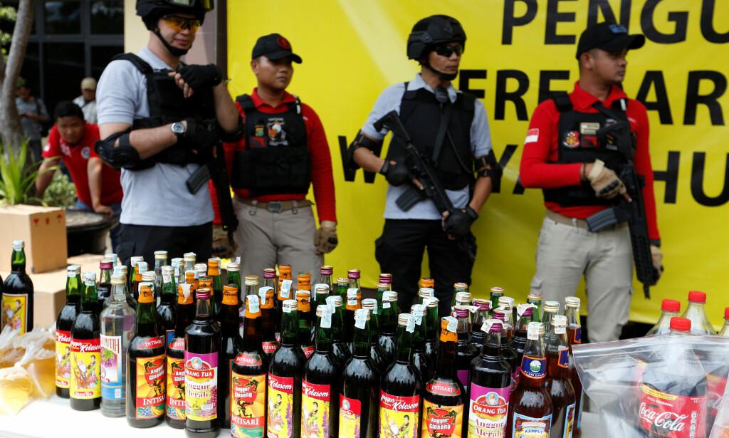 OMFATTENDE: Politiet legger fram noen av bevisene etter metanolholdig sprit ble beslaglagt i Jakarta i Indonesia. Nær 100 personer er så langt døde av metanolforgiftning. Foto: Reuters / NTB Scanpix