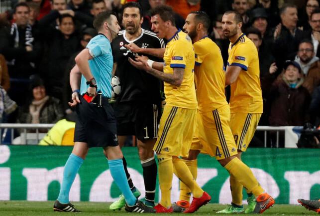OPPHETEDE FØLELSER: Michael Oliver ble jaget rundt av Juventus-spillerne etter at han hadde gitt Real Madrid straffe. Det førte til rødt kort for keeper Gianluigi Buffon (i sort). Foto: NTB scanpix
