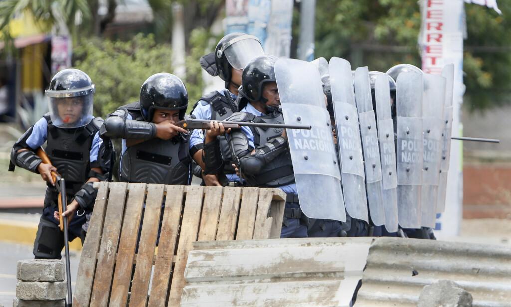 OPPRØR: Nicaraguansk opprørspoliti barket sammen med studenter som protesterte på tredje dagen i Nicaraguas hovedstad Managua fredag. Foto: Alfredo Zuniga / AP / NTB scanpix