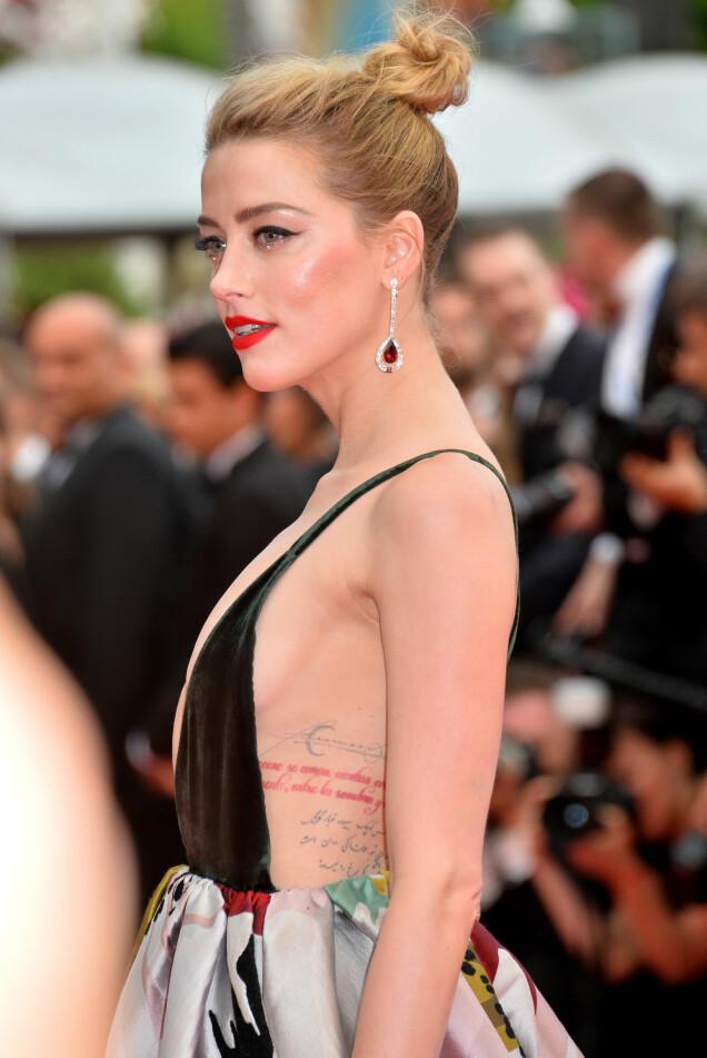 <strong>SYNLIGE TATOVERINGER:</strong> Flere av Amber Heards fargerike tatoveringer var synlige som følge av kjolens avslørende overdel. Foto: FeatureflashSHM/REX/Shutterstock/ NTB scanpix