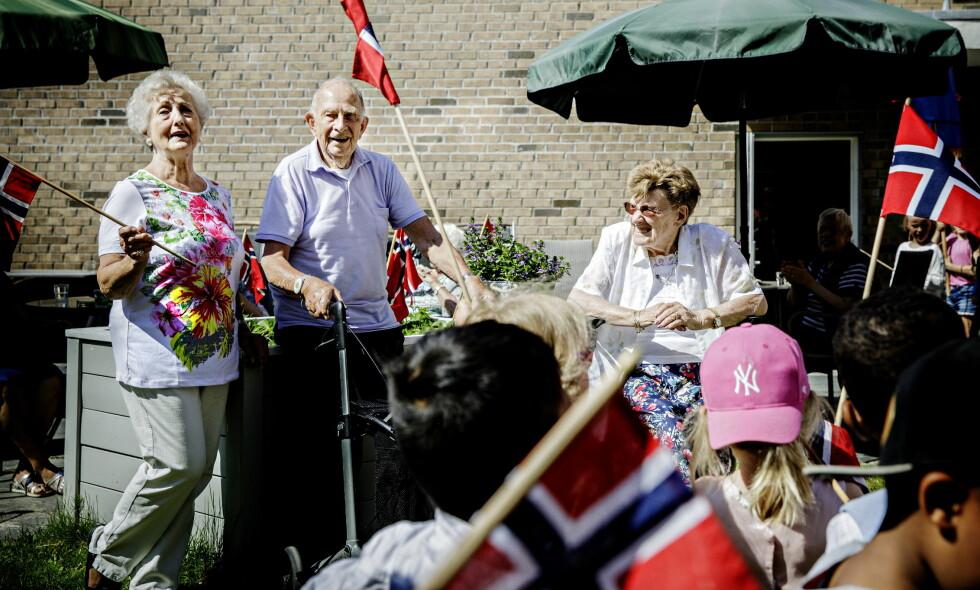 KOSER SEG UANSETT: Beboere på Ensjøtunet i Oslo, Berit Bergersen (82), Reidar Næss (89) og Solveig Westby (92) fikk onsdag besøk av Fyrstikkaleen barnehage og savner ikke NRK. Foto: Nina Hansen / Dagbladet
