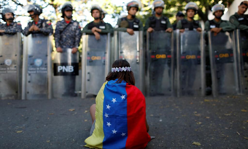 I DYP KRISE: Venezuela er inne i en svært dyp økonomisk og politisk krise. Hva skjedde i det oljerike landet som gjorde at det kunne gå så galt? Her ei jente med venezeluansk flagg foran sikkerhetsstyrker i landets hovedstad Caracas i januar i år. Foto: REUTERS / Marco Bello / NTB Scanpix