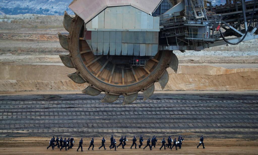 DEMONSTRASJONER: Opprørspoliti løper forbi en utgravningsmaskin ved RWEs kullgruve Garzweiler, under en demonstrasjon mot gruva i november 2017. Foto: Wolfgang Rattay / Reuters / NTB Scanpix