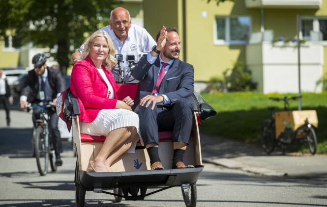 ET FORBILDE: Kronprinsesse Mette-Marit og kronprins Haakon fikk skyss i en elsykkel av 80 år gamle Harald Øyen under et besøk på Sagene i Oslo i mai 2018 - og vi mener jo selvfølgelig at det er fantastisk at eldre, småbarnsforeldre og folk med helseplager benytter elsykkel for å komme seg frem. Vi andre - vi får bite tennene sammen og komme oss opp bakken på vanlige sykler, mener KK-journalist Malini Bjørnstad. FOTO: NTB Scanpix