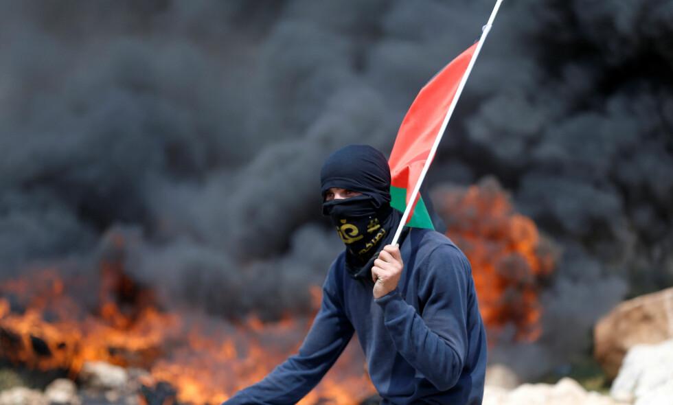 OKKUPERT: En ung person med et palestinsk flagg deltar i demonstrasjoner mot en av flere israelske botsettinger i mars i fjor. Human Rights Watch hevder i en ny rapport at oljefondet har investert i flere israelske banker som alle driver business på okkupert palestinsk land. Foto: Mohamad Torokman / Reuters / NTB Scanpix