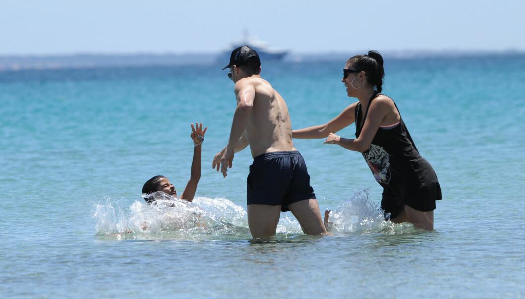 LATTER: Da Cristiano Ronaldo kastet sønnen i vannet var det til stor glede for alle tre, som man kan se på smilene deres. Foto: Splash News / NTB Scanpix