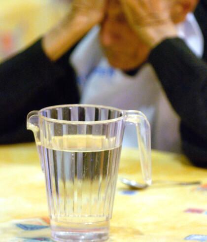 """DRIKKER IKKE NOK: En eldre mann sitter ved siden av en vannkanne """"L'Eclaircie"""" eldrehjem i La Motte Servolex, i Frankrike tirsdag 28. juni 2005, men uten å drikke noe. Det var 38 grader den dagen. To år tidligere døde titusener av eldre i hetebølge. Foto: NTB/Scanpix"""