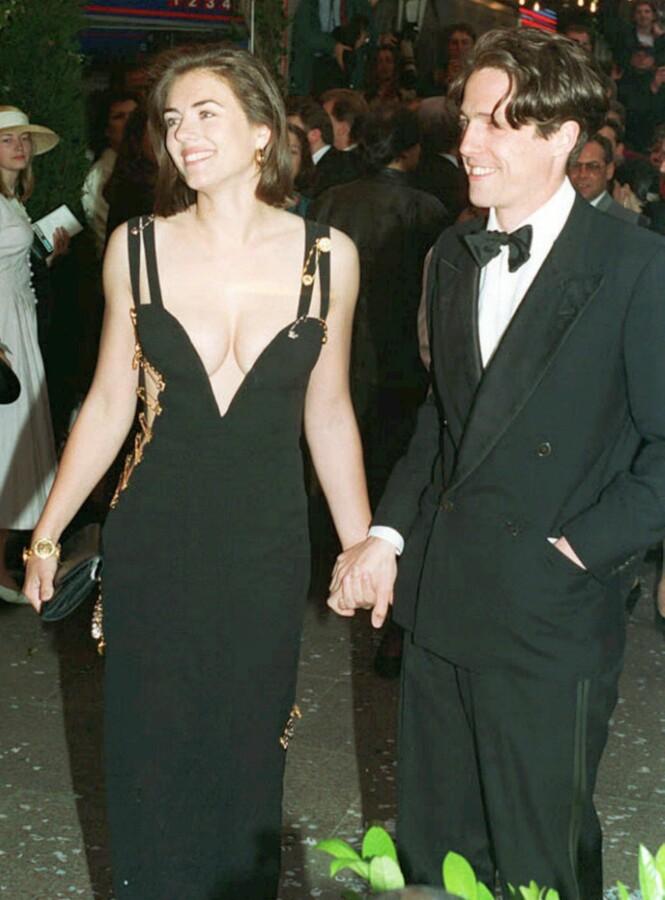 IKONISK KJOLE: Det var med denne kjolen at Liz Hurley stjal all oppmerksomheten i 1994. Her på date med sin daværende kjæreste Hugh Grant (57) på premieren for hans film «Fire bryllup og en gravferd».Foto: NTB Scanpix