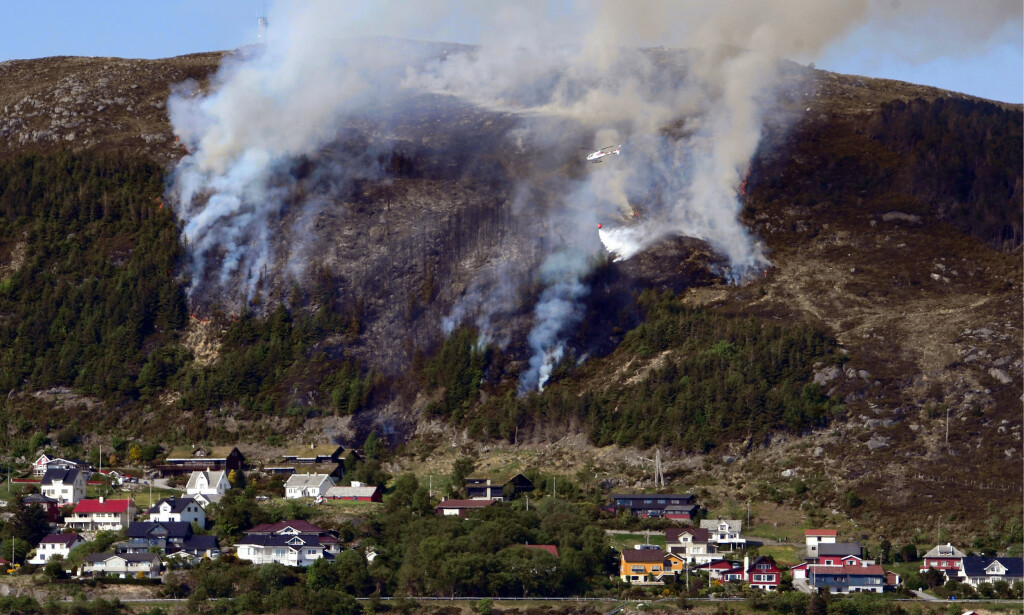 SKOGBRANN: Brannhelikopter ble satt inn i slukkingen av en brann spredde seg i vegetasjonen på Remøya i Herøy kommune i Møre og Romsdal 28. mai. Foto: Knut Arne Aarset / Sunnmørsposten / NTB scanpix