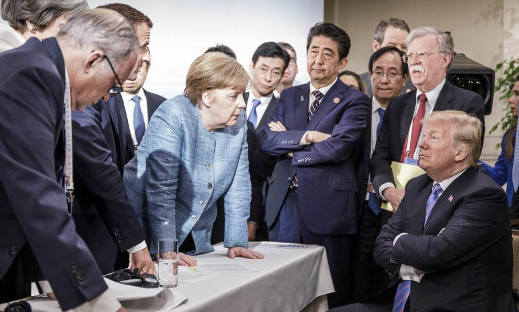 TRUMP MOT VERDEN: Det talende bildet fra G7-toppmøtet i Canada viser Donald Trump omgitt av statsledere med Tysklands Angela Merkel i spissen. Kort tid etter bildet ble tatt trakk han USA fra sluttavtalen på vei til det historiske møte med Nord-Koreas leder Kim Jong-un i Singapore. Foto: Jesco Denzel / dpa / NTB Scanpix