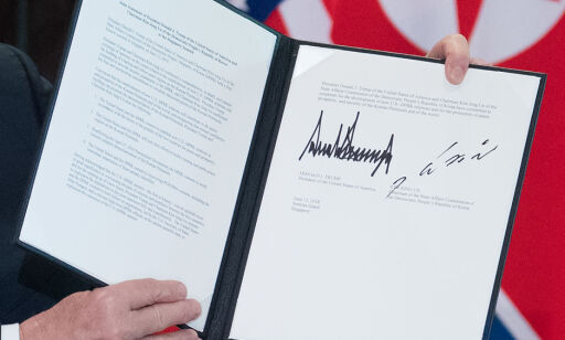 US President Donald Trump holds up a document signed by him and North Korea's leader Kim Jong Un following a signing ceremony during their historic US-North Korea summit, at the Capella Hotel on Sentosa island in Singapore on June 12, 2018.  Donald Trump and Kim Jong Un became on June 12 the first sitting US and North Korean leaders to meet, shake hands and negotiate to end a decades-old nuclear stand-off. / AFP PHOTO / SAUL LOEB